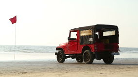 Truck standing on sandy beach, with man passing. stock footage