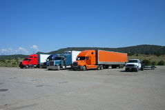 Truck Stop. Trucks lined up in a row at an interstate truckstop, with tree lined hills behind Royalty Free Stock Photo