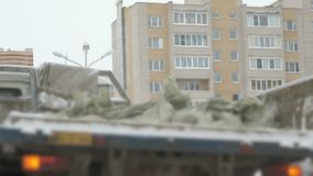 Truck takes out construction garbage in bags. In the back in the winter, high-rise buildings stock video