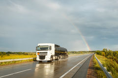 Truck with a tank & x28;cistern& x29; moving on a wet road. Truck with a tank & x28;cistern& x29; moving on a wet road after the rain. Rainbow is seen on Stock Photography