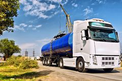 Truck with a tank for transportation of petroleum products. A truck with a tank for transportation of petroleum products traveling on a dusty road at an Royalty Free Stock Images