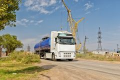 Truck with a tank for transportation of petroleum products. A truck with a tank for transportation of petroleum products traveling on a dusty road at an Royalty Free Stock Image