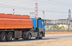 Truck with tank for transportation of petroleum products. Drive on the road in front of refinery Stock Photos