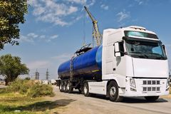 Truck with a tank for transportation of petroleum products. A truck with a tank for transportation of petroleum products traveling on a dusty road at an Stock Photos