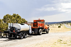Highway repair by Tar Spreader. Truck and tar spreader parked along highway preparing to repair road Stock Photos