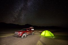 Truck and tent on flat dirt with starry sky overhead Stock Image