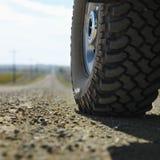 Truck tire on gravel road.