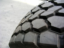 Truck tires. Macro view of truck tires with deep tread, road in background royalty free stock image