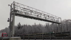 Truck toll system. Trucks pass a control gantry of german truck toll system on Autobahn A3 on January 20, 2015. Germany's LKW-Maut is a toll for goods vehicles stock video footage
