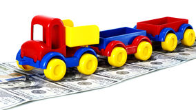 Truck toy on the road from money on white background Stock Photography