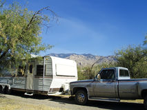 Truck and trailer. A truck and camping trailer parked at a scenic camping site with mountains in the background Stock Image