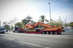 Truck trailer carrying excavator machine. A truck on a road travelling and carrying an excavator machine Stock Image