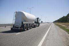A truck with a trailer is driving along the highway stock photos
