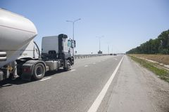A truck with a trailer is driving along the highway royalty free stock photos