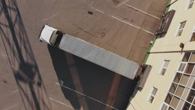 Cargo transport container for loading goods at the seaport, top view. Truck with transport container approaching warehouse in terminal for loading goods