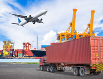 Truck transport container and cago plane flying above ship port. With working crane loading bridge in shipyard for logistic import export concept royalty free stock images