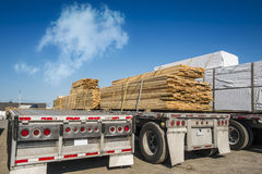 Truck transporting wood. Truck transporting plank of woods with a nice blue sky Royalty Free Stock Photo