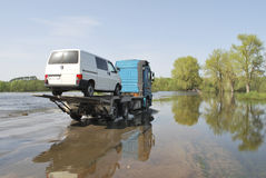 Truck transports passenger car which appeared over the river ban Royalty Free Stock Images