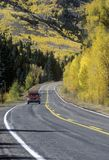 A truck traveling in autumn on Route 145 in Colorado Royalty Free Stock Image