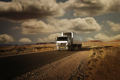 Truck traveling on a road in the desert at sunset Royalty Free Stock Images