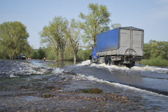 Truck travels across the river which came out of its banks and f Stock Images