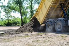 Truck unloading dirt and sand. Photo was taken on a nice sunny day. Time: about noon. Photo was taken on a construction site near football stadium Spartak Royalty Free Stock Image