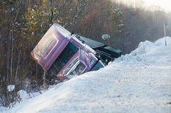 Truck in winter road accident. A truck lying sideways after winter road accident stock images