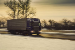Truck on winter road. Truck on country winter road in motion. Evening time background Royalty Free Stock Images
