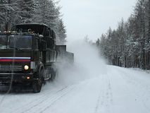 Truck on winter road. 10 November 2009 Northern region of Russia. The truck trailer driven by the emergency vehicle. High plume of snow lifted the truck Royalty Free Stock Photography