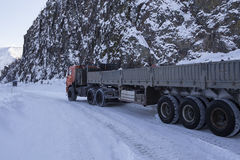 Truck on winter road under a rock. Royalty Free Stock Photography