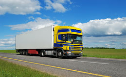 Truck With Blue-yellow Cabin Moving On Highway. Royalty Free Stock Photography