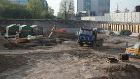 Truck worker excavator. Truck full of dirt driving and man disembark step out circa May 2013 in Vilnius, Lithuania. Excavator dig ground in construction site stock video