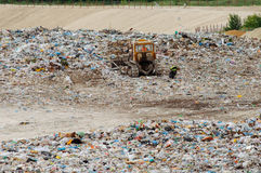 Truck working in landfill with birds looking for food. Garbage on the city dump. Soil pollution. Environmental protection. Stock Images