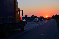 Trucker, η εθνική οδός και το ηλιοβασίλεμα Στοκ Φωτογραφίες