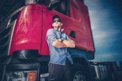 Trucker and His Semi Truck. Caucasian Trucker in His 30s and His Red Euro Semi Truck Tractor. Transportation and Shipping Industry Stock Photo