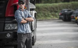 Trucker and His Semi Truck. Caucasian Driver in His 30s in the Delivery Hub. Transportation Theme royalty free stock images
