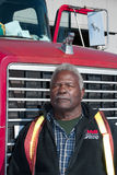 An African American man stands in front of a Mack truck Stock Photo