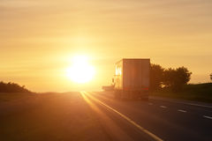 Trucking at sunrise on an empty road Royalty Free Stock Photo