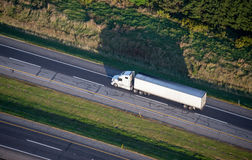 Trucking and Transportation aerial. While semi trailer truck delivers freight and services down a US interstate. Aerial photo stock image