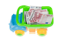 Truckload of money. Plastic toy lorry truck filled with euro notes, seen from above. Isolated on white Royalty Free Stock Photography