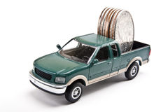 Truckload of Money. Miniature pick-up truck hauling quarters in the bed Stock Images