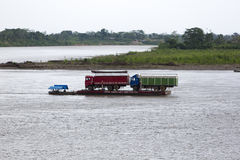 Trucks on a barge pulled by a motorboat in Rurrenabaque, Bolivia Stock Photos