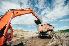 Trucks being loaded during highway construction site. Details of excavator scoop doing earthmoving works. Roadworks. Dumper trucks being loaded during highway Royalty Free Stock Image