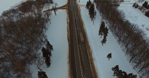 Trucks and cars driving on winter highway. Aerial view. Truck driving on highway at winter evening day, Dirty asphalt road in a snowy field or forest stock video footage