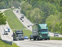 Trucks and traffic on hilly highway Stock Images