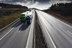 Trucks deriving on scenic highway at sunset Stock Images