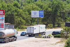 Trucks with different cargos go out of town for a bypass road Royalty Free Stock Photography