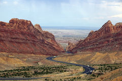 Trucks drive along road that winds through Spotted Wolf Canyon Stock Images