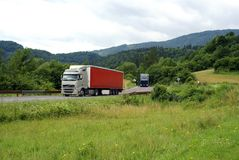 Trucks driving on country-road. With mountains on background Royalty Free Stock Photos