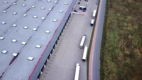 Trucks are Driving to Logistics Center. Aerial Shot./ Storage Building/ Loading Area where Many Trucks Are Loading/ Unloading Merc. Handise. Logistics stock video